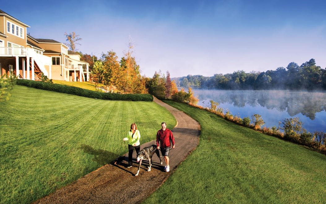A couple walking a dog along a dirt path in the morning with homes on a small hill on the left and a lake on the right