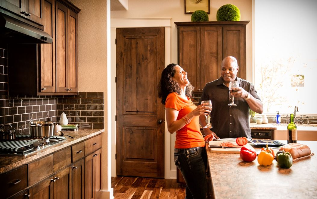 A couple laughing while drinking wine in their new kitchen