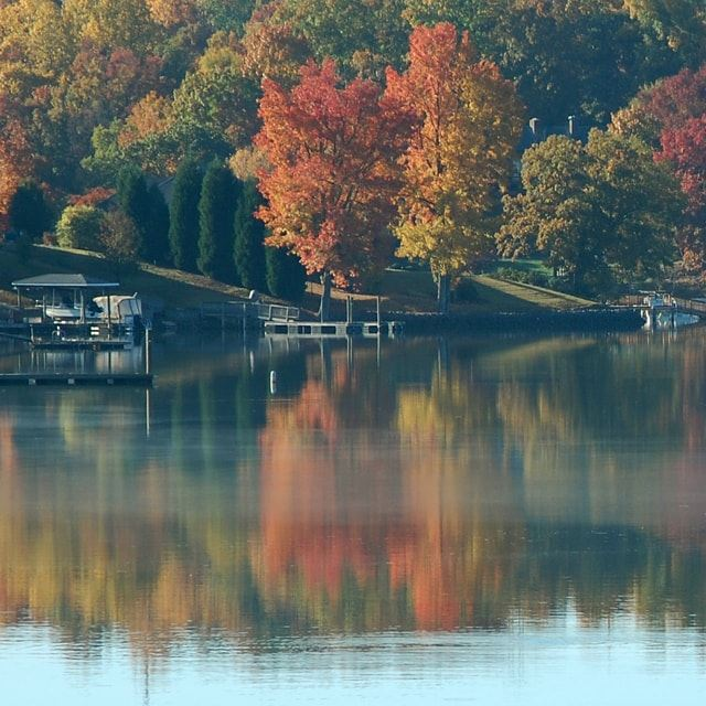 Calm lake with docks and colorful trees in the background during fall