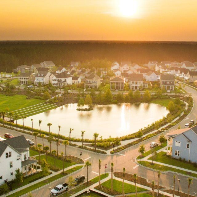 Aerial view of Nexton community with pond in the center and sun setting behind the community