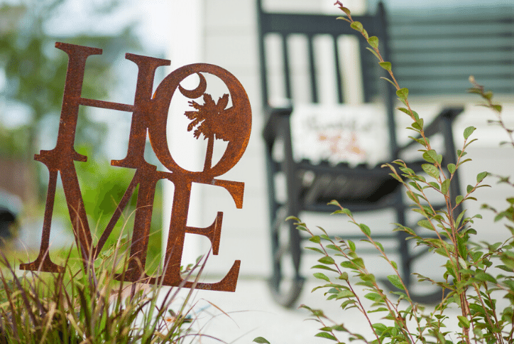 Rusted metal sign that says Home in front of a rocking chair on a porch