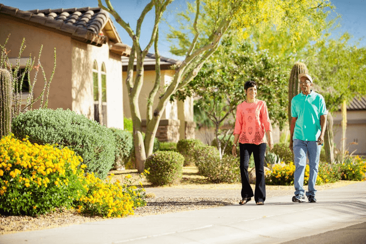 Couple walking in front of desert landscape and homes