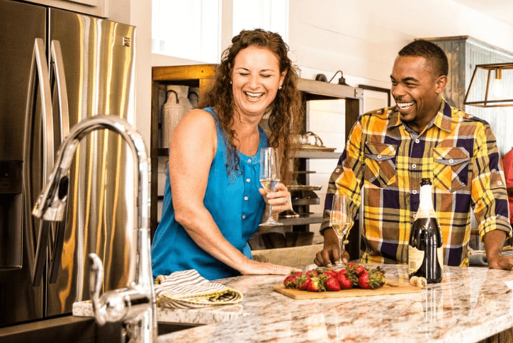 Woman and man enjoying fresh strawberries and a glass of champagne in a modern kitchen