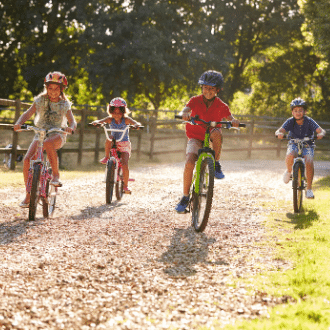 Four children on bicycle ride on countryside trail