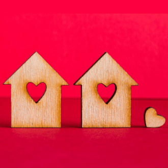 Two small wood home figurines with hearts cut out of the middle